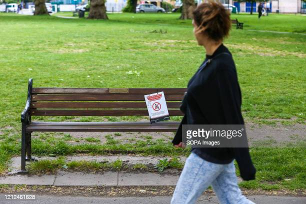 Woman looks at 'You should only use this bench for a short rest while exercising' poster on a north London park bench with a graffiti of an...
