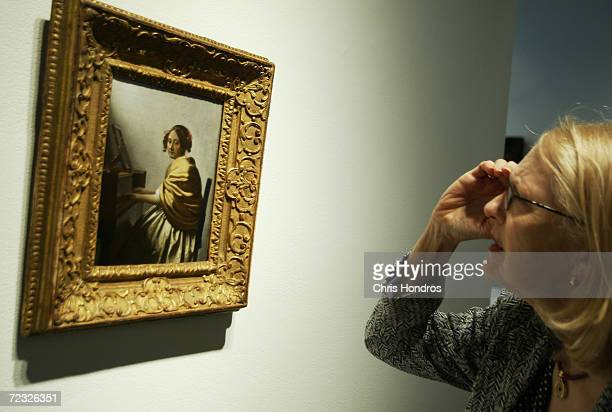 A woman looks closely at Johannes Vermeer's painting Young Woman Seated at the Virginals soon up for auction by Sotheby's auction house May 24 2004...