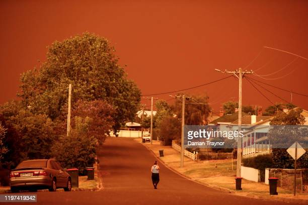 A woman looks down her street as the sky turns red from the fires on January 04 2020 in Bruthen Australia Two people are dead and 28 remain missing...