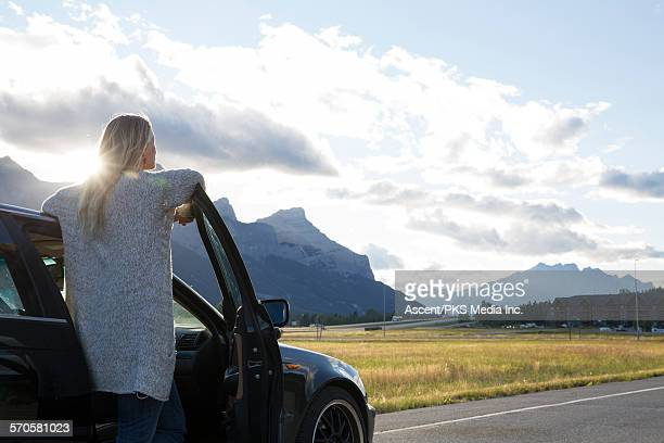Woman looks down highway from car door, sunrise