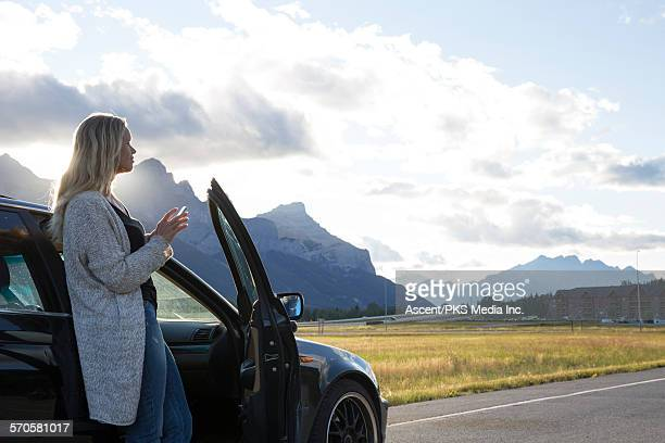 Woman looks down highway while texting, sunrise
