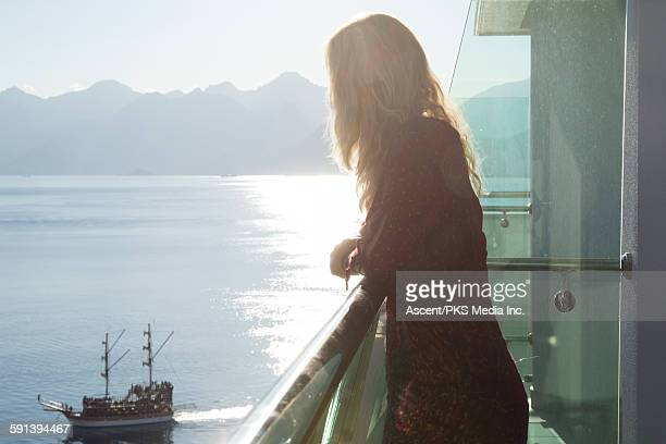Woman looks down towards passing ship, from hotel
