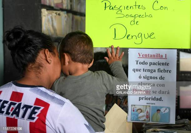 A woman looks for medical attention for her child allegedly affected by dengue fever at the Alonso Suazo Health Center in Tegucigalpa on July 22 2019...