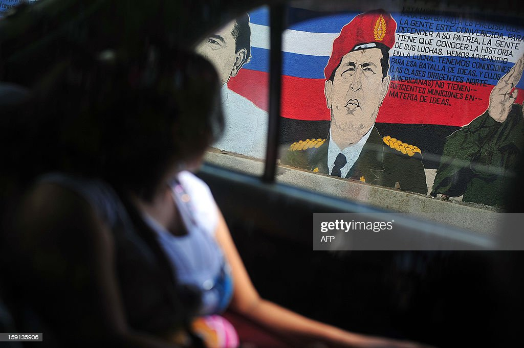 A woman looks from a taxi at a mural portraying Venezuelan President Hugo Chavez in Managua on January 8, 2013. The President of the Venezuelan National Assembly Diosdado Cabello announced today that due to health reasons, Chavez will not be able to take the oath to be sworn in for a fourth term in office next January 10. A constitutional fight intensified with the government planning a massive show of support in the streets on the day he is supposed to be sworn in. Chavez, who underwent his fourth round of cancer surgery in Havana nearly a month ago, is suffering from a severe pulmonary infection that has resulted in a respiratory insufficiency.AFP Photo/Hector RETAMAL