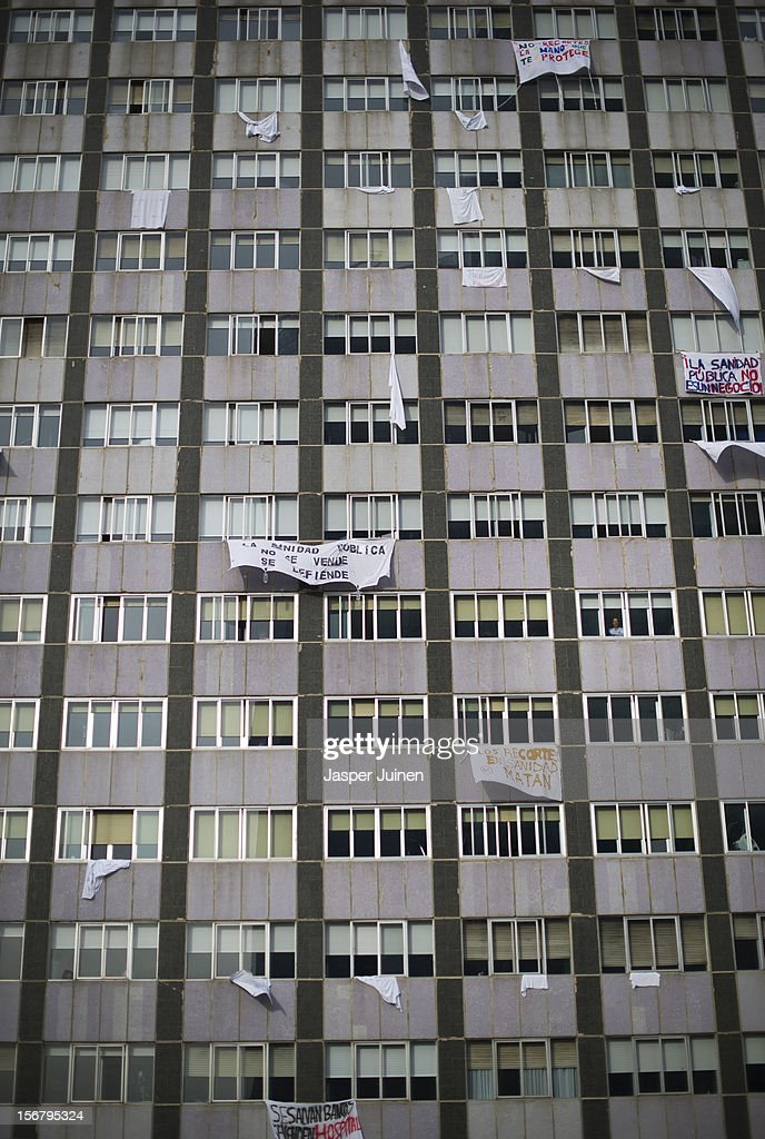 A woman looks from a window as banners hang from La Paz hospital on November 21, 2012 in Madrid, Spain. Doctors and nurses in the Spanish capital are preparing for a four day strike to protest against the privatisation of some parts of Spain's national health service.