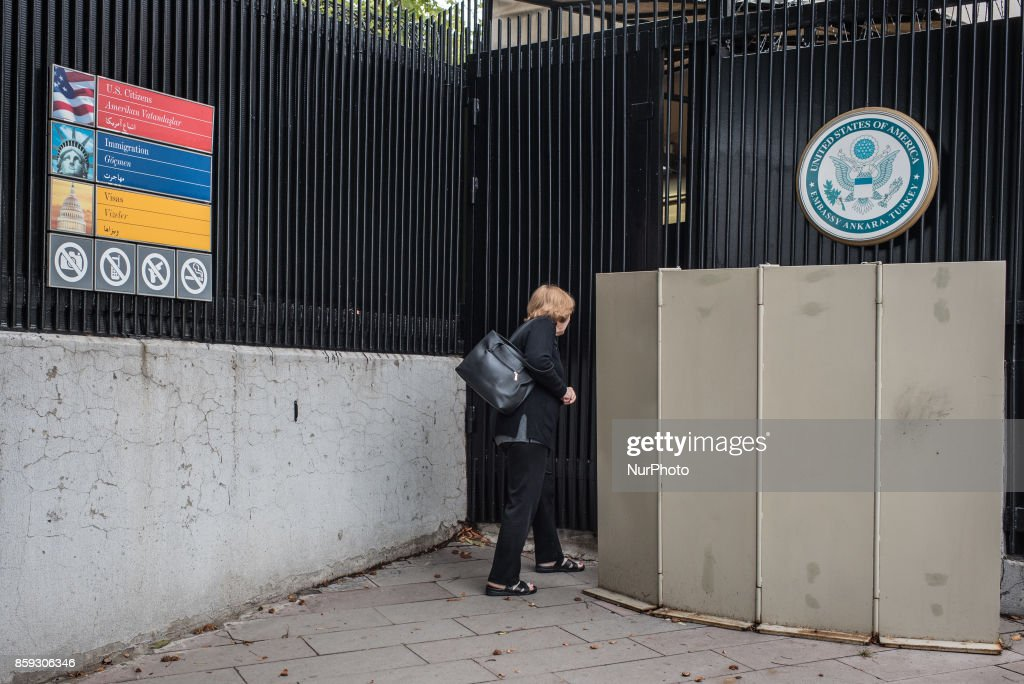 A woman looks in the closed entrance of the United States Embassy in Ankara, Turkey, on Monday, 9 October 2017. American visa services were halted at US missions in Turkey following the detention of US consulate personnel in Istanbul, a move that sparked a diplomatic backlash between both countries.