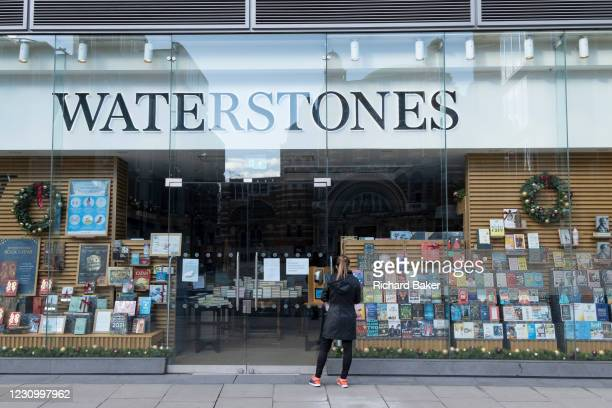 Woman looks in the window of The Victoria branch of closed bookseller chain, Waterstones during the third lockdown of the Coronavirus pandemic, on...