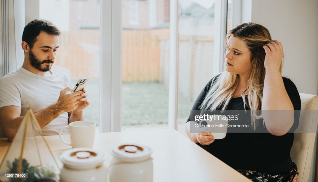 A woman looks insecure as her partner ignores her to look at his phone : Stock Photo
