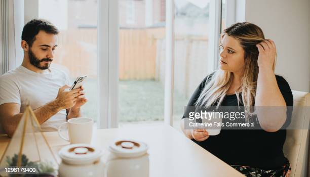 a woman looks insecure as her partner ignores her to look at his phone - couple relationship stock pictures, royalty-free photos & images