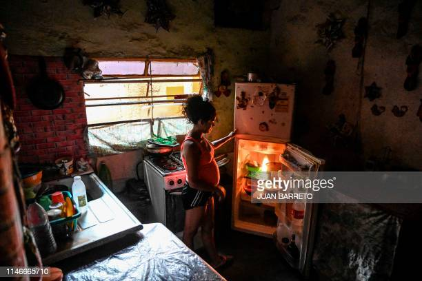 A woman looks inside a refrigerator at her house in Petare neighbourhood Caracas on March 24 2019 Venezuela is blighted by the worst economic crisis...
