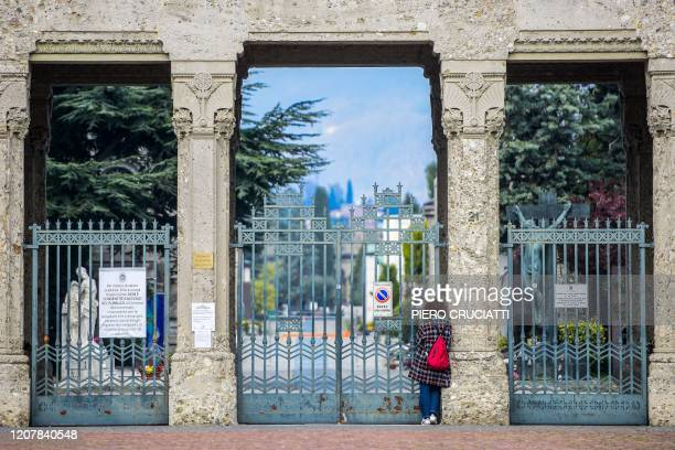 A woman looks inside the closed Monumental Cemetery of Bergamo Lombardy on March 20 2020 during the country's lockdown aimed at stopping the spread...