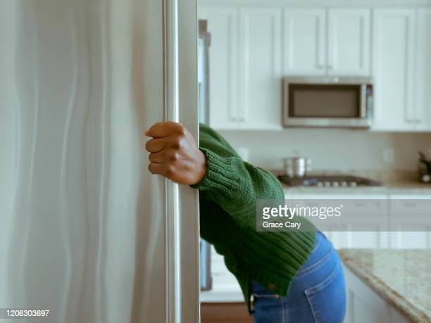 woman looks into refrigerator for healthy snack - pantalon noir photos et images de collection