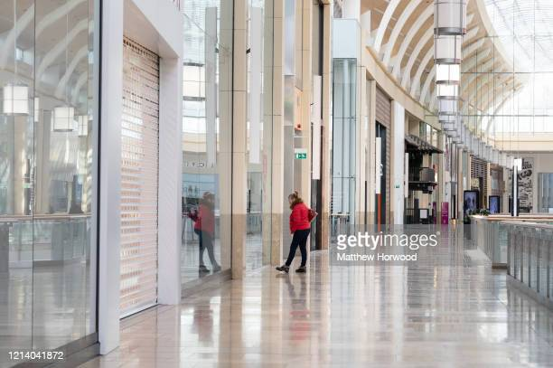 Woman looks into the window of a closed shop at St. David's shopping centre on March 22, 2020 in Cardiff, United Kingdom. On Friday UK Prime Minister...