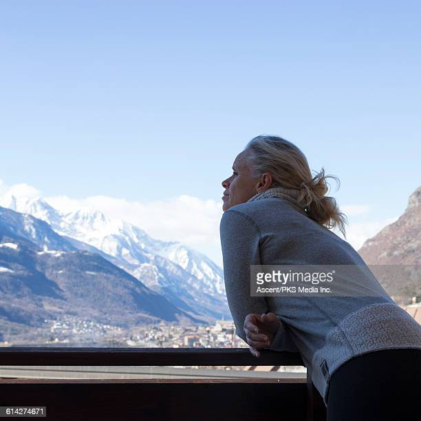 Woman looks off to mountains from veranda