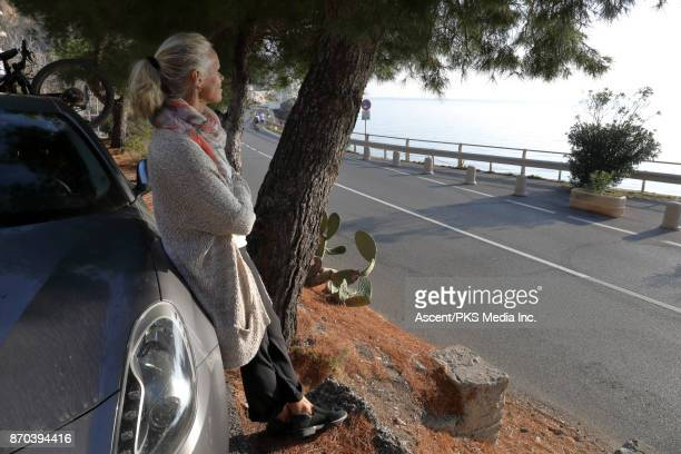 Woman looks off to sea and pines from car, roadside