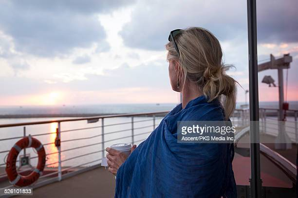 woman looks off to sunset form boat deck, railing - shawl stock pictures, royalty-free photos & images