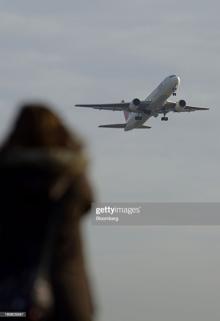 A woman looks on as a Japan Airlines Co. (JAL) aircraft takes off at Haneda Airport in Tokyo, Japan, on Sunday, Feb. 3, 2013. Japan Airlines, the nation's largest carrier by market value, is scheduled to release earnings on Feb. 4. Photographer: Akio Kon/Bloomberg via Getty Images