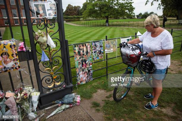 A woman looks on as floral tributes photographs and messages sit outside an entrance gate to Kensington Palace ahead of the 20th anniversary of the...