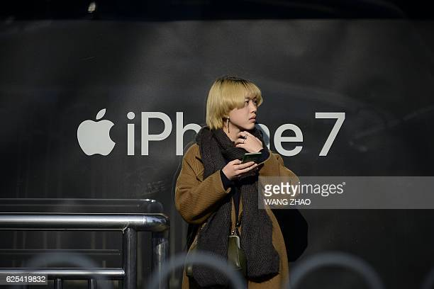 A woman looks on as she stands in front of a billboard promoting Apple's iPhone 7 at a bus stop in Beijing on November 24 2016 China will be handed...