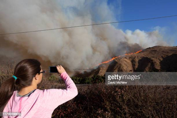 A woman looks on as the Easy Fire approaches on October 30 2019 near Simi Valley California The National Weather Service issued a rare extreme red...