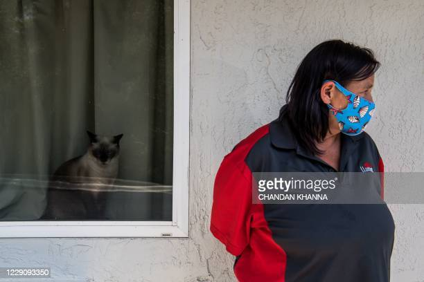 Woman looks on as the head of the Kissimmee-Poinciana Homeless Outreach, Barbie Austria, donates essentials to jobless living in a motel in...