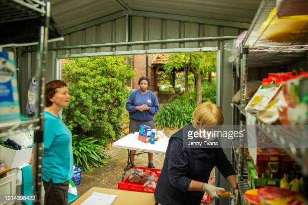 A woman looks on as volunteers Margaret Baseley and Kerin Brown handle food items at St Paul's Anglican Church in Burwood on March 24 2020 in Sydney...