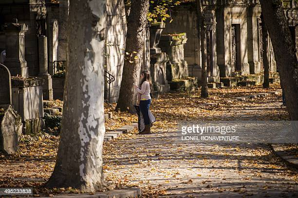 A woman looks on at the Pere Lachaise cemetery on November 1 2015 in Paris during the AllSaints Day AFP PHOTO / LIONEL BONAVENTURE
