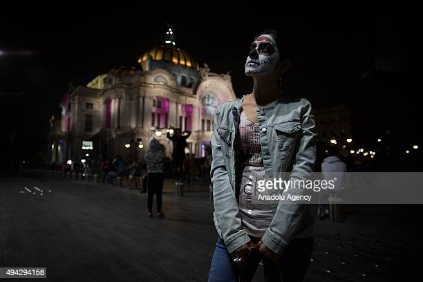 A woman looks on during Procession of the Catrinas in Mexico City Mexico on October 25 2015 The Catrina is a figure of a skeleton wearing an elegant...