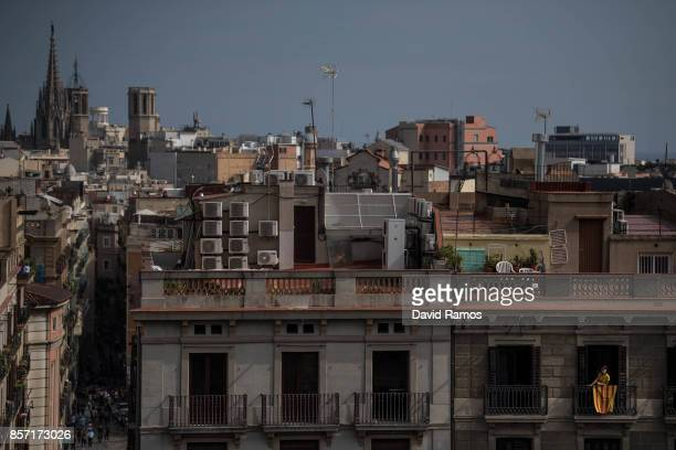 A woman looks on from her balcony draped in a Catalan flag during a regional general strike to protest against the violence that marred Sunday's...