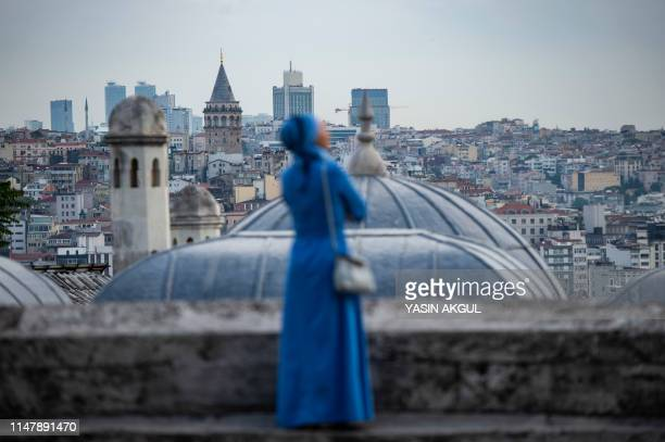 TOPSHOT A woman looks on from the terrace of the Suleymaniye mosque after Eid alFitr prayers at the Suleymaniye mosque on June 4 2019 in Istanbul...