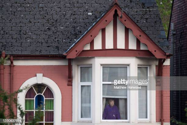 Woman looks on from the upstairs window of a house opposite the Royal Gwent Hospital as people gather to clap key workers on April 23, 2020 in...