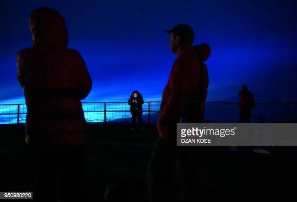 A woman looks on her mobile phone as she stands by the sea during a dawn service marking the 103rd anniversary of ANZAC Day in Canakkale Turkey on...