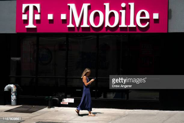 Woman looks on her phone as she walks past a T-Mobile store on Sixth Avenue in Manhattan on July 26, 2019 in New York City. On Friday, the U.S....