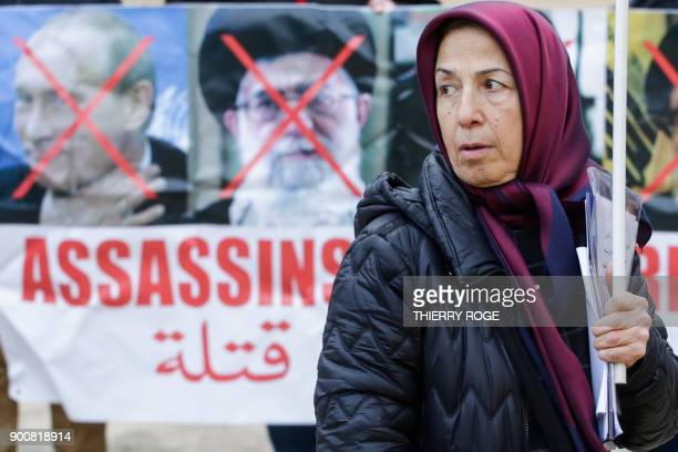 A woman looks on next to the crossed out portraits of Russian President Vladimir Putin and Iranian supreme leader Ayatollah Ali Khamenei on January 3...