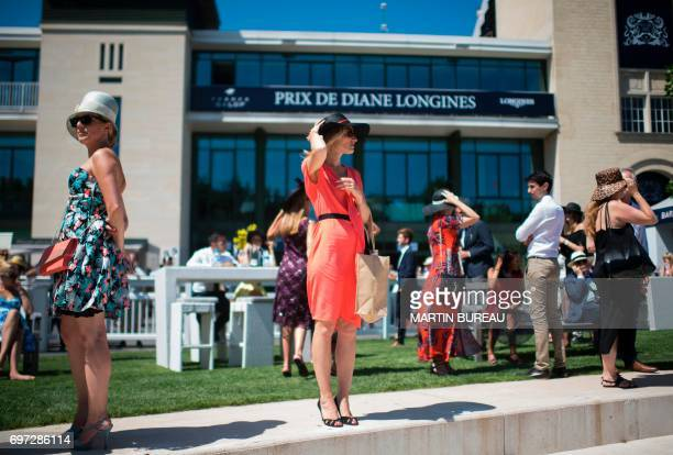 Woman looks on prior to the start of the Prix de Diane, a 2,100-meters flat horse race, on June 18, 2017 at the Chantilly hippodrome, north of Paris....