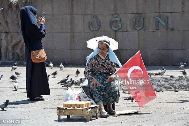 A woman looks on while selling food for pigeons in the Kizilay Square in Ankara on July 23 2016 Turkey's EU minister said July 23 that the failed...