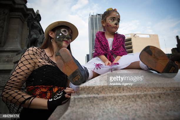 A woman looks on with her daughter during Procession of the Catrinas in Mexico City Mexico on October 25 2015 The Catrina is a figure of a skeleton...