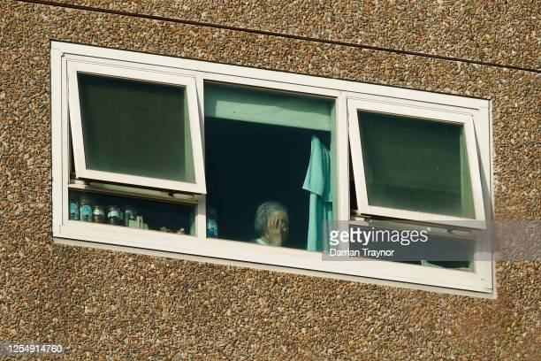 A woman looks out a window of the North Melbourne Public Housing tower complex on July 08 2020 in Melbourne Australia Further lockdown measures for...