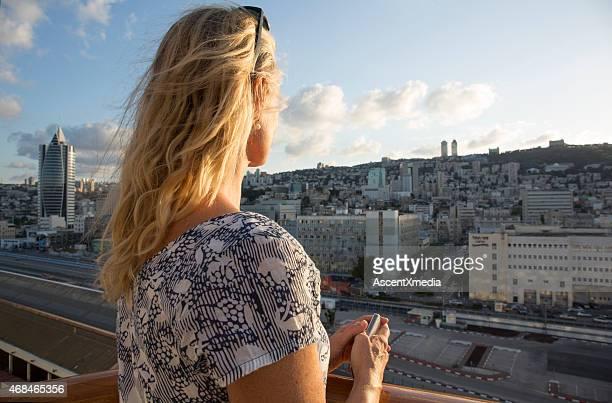 女性の街の風景を見晴らす日の出