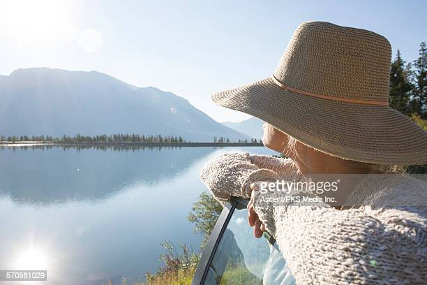 woman looks out across lake from car door - wide brim stock pictures, royalty-free photos & images