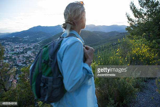 Woman looks out at hillside in Liguria, Italy.