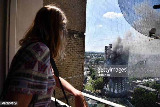 A woman looks out at the 24 storey residential Grenfell Tower block in Latimer Road West London in the early hours of this morning on June 14 2017 in...