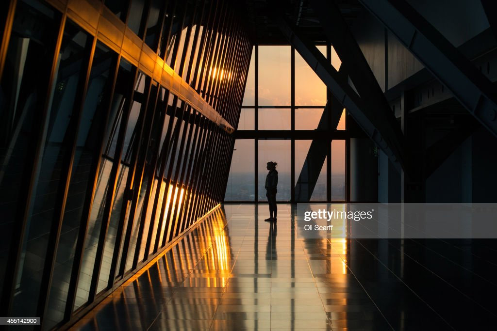 A woman looks out at the London skyline from an upper floor of a newly constructed skyscraper, The Leadenhall Building, as the sun sets on September 9, 2014 in London, England. The skyscraper, located in the City of London, has been dubbed the 'Cheesegrater' for its distinctive shape. The building stands at 224 meters high and was designed by 'Rogers Stirk Harbour + Partners'.