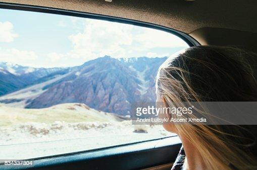 Woman looks out car window in mountain landscape