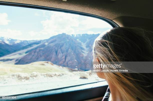 Woman looks out car window in mountain landscape