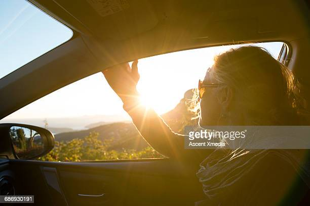 Woman looks out car window towards sunrise