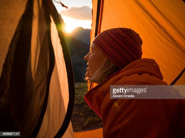 Woman looks out form inside tent, mtn sunrise