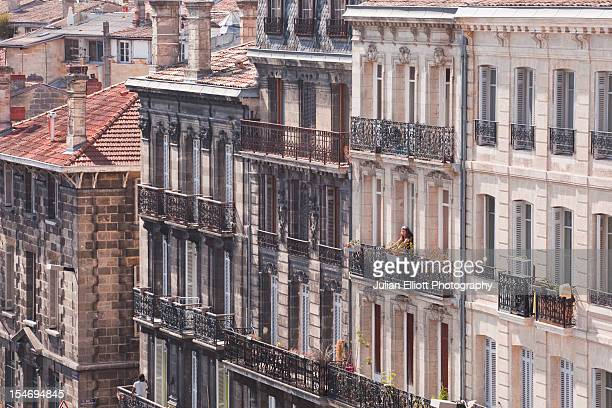 A woman looks out from a balcony across Bordeaux.