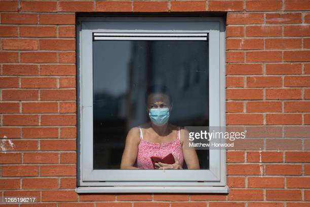 Woman looks out from a window wearing a surgical mask as UK Prime Minister Boris Johnson visits a construction site on August 11, 2020 in Hereford,...