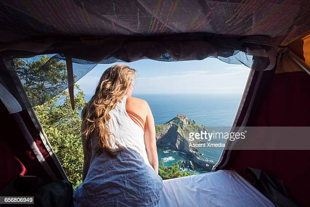 woman looks out from tent to sea vista below - pais vasco fotografías e imágenes de stock